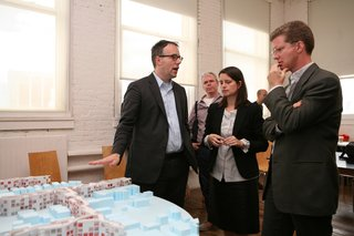 """""""Foreclosed"""" Open Studio at PS1 - Photo 1 of 7 - U.S. Secretary of Housing and Urban Development Shaun Donovan (right) discusses MOS's proposal with Michael Merideth and Hilary Sample."""