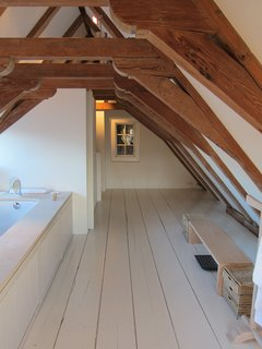 25 Homes With Exposed Wood Beams: Rustic to Modern - Photo 25 of 25 - A very steep and narrow flight of stairs leads to one of the best parts of the room at the Dylan in Amsterdam: a big bathroom tucked into the attic that has original wooden beams arching overhead.