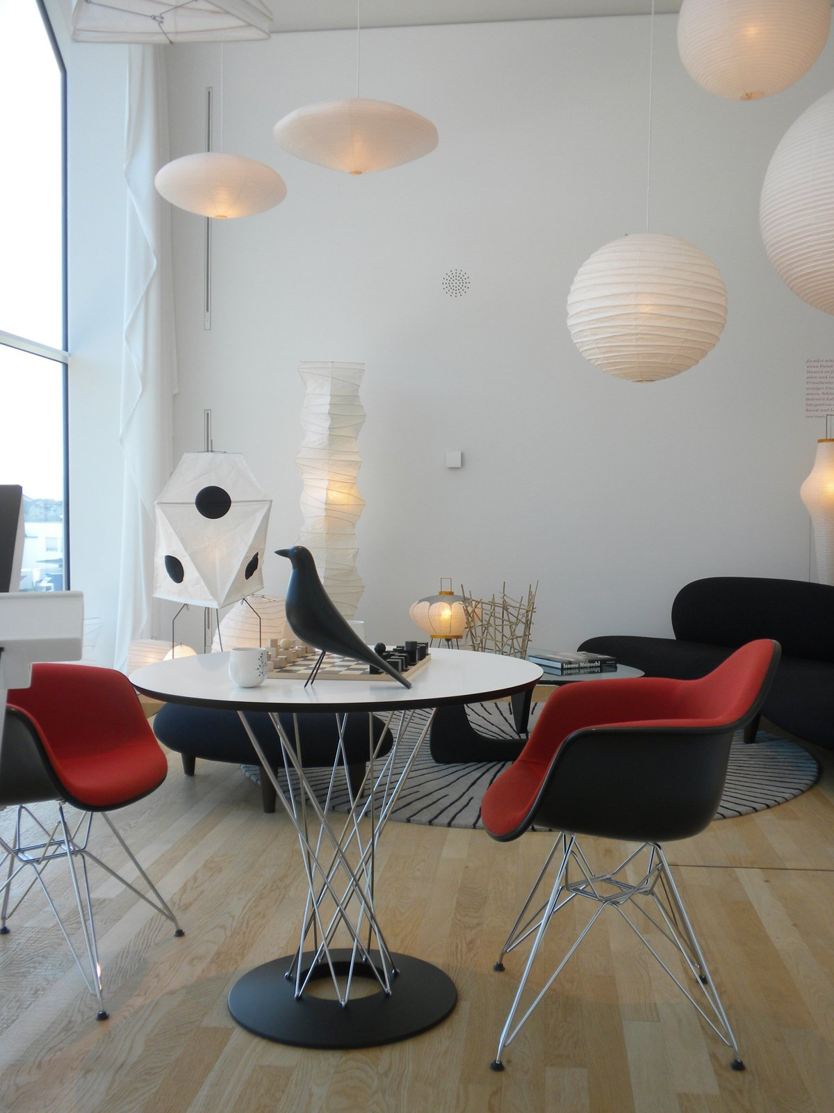 This living room setting is devoted to Isamu Noguchi, with a hit of Eames in the DAR Eames Plastic Armchairs and Eames House Bird atop the Noguchi Dining Table. In the background are the Freeform Sofa and Ottoman, Noguchi Table, and assorted Akari lamps by the designer.  Inside the VitraHaus by Miyoko Ohtake