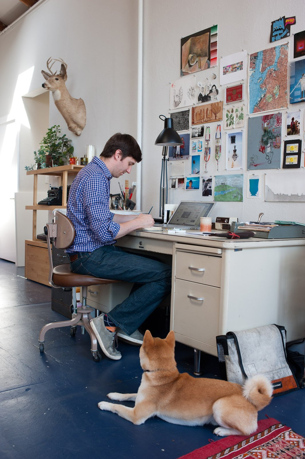 "A familiar scene in the Benoit home: Peter paints at the Steelcase desk—""I do all my work here,"" he says—while Ando sits nearby, waiting for attention. Tagged: Office, Desk, Shelves, Chair, and Linoleum Floor.  Photo 12 of 19 in Storage Savvy Renovation in Emeryville"