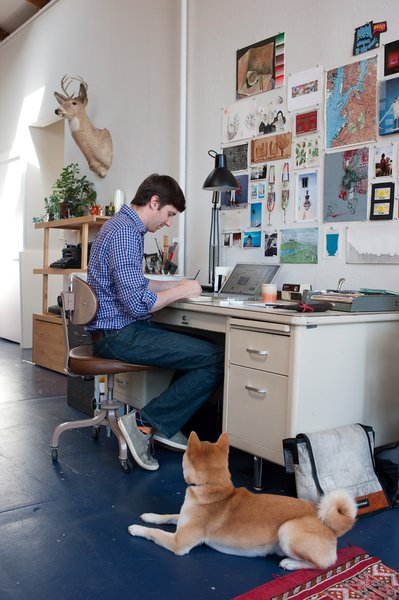 "A familiar scene in the Benoit home: Peter paints at the Steelcase desk—""I do all my work here,"" he says—while Ando sits nearby, waiting for attention."