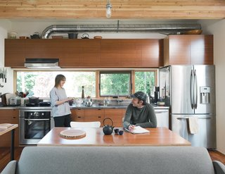 Bovee and Kirkpatrick eat at the table he designed. The cooktop, oven, and dishwasher are by Bosch; Bren Reis of Earthbound industries made the cabinets.