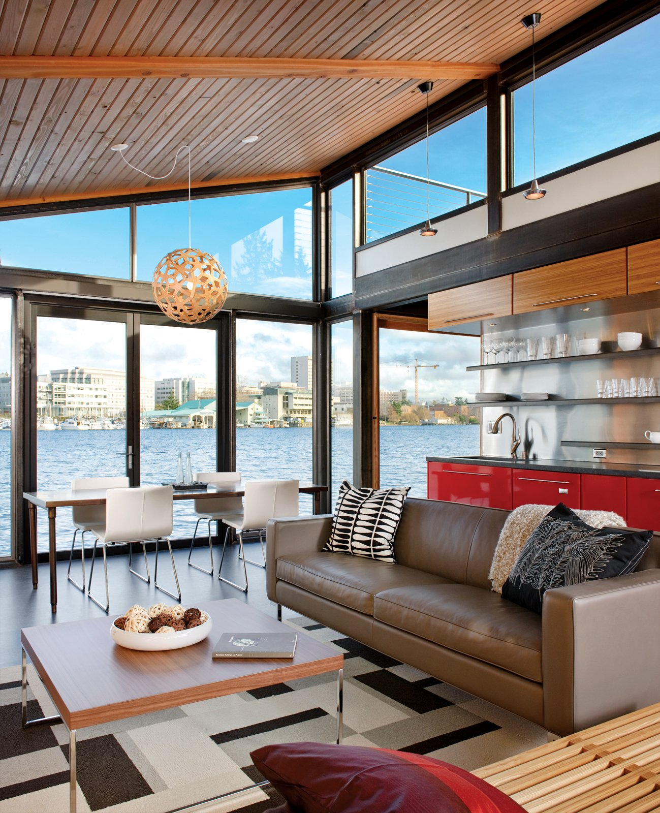 The floor-to-ceiling windows at either end of a Seattle boathouse allow light to stream through the entire 1,000-square-foot space.  Photo 1 of 2 in A Renovated Boathouse on Seattle's Portage Bay