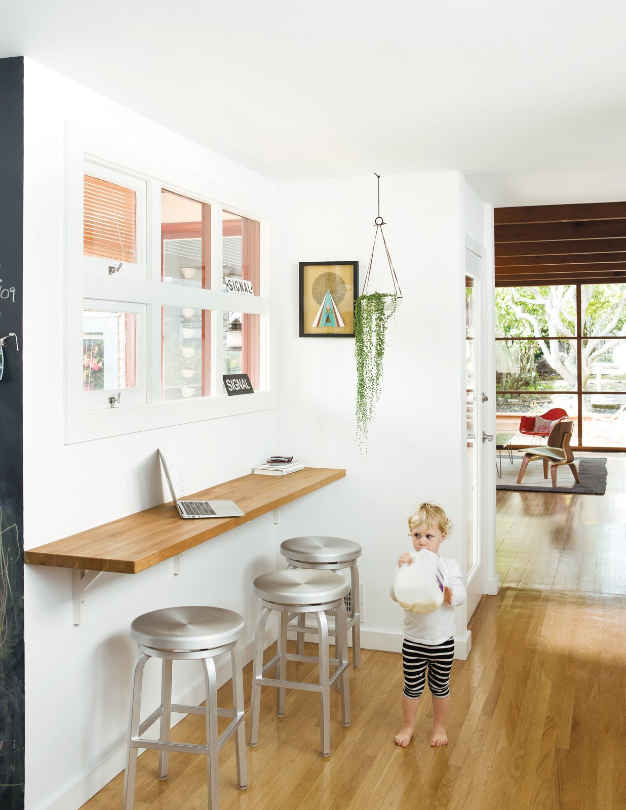 A wall-mounted oak bar is where Siminovich and Kerner drop their keys, pound away on their laptops, and occasionally eat a quick meal with Matilda, their two-year-old daughter. Tagged: Dining Room, Bar, and Stools.  Photo 7 of 10 in A Couple Tackles Conversion Challenges and Builds a Modern Renovation