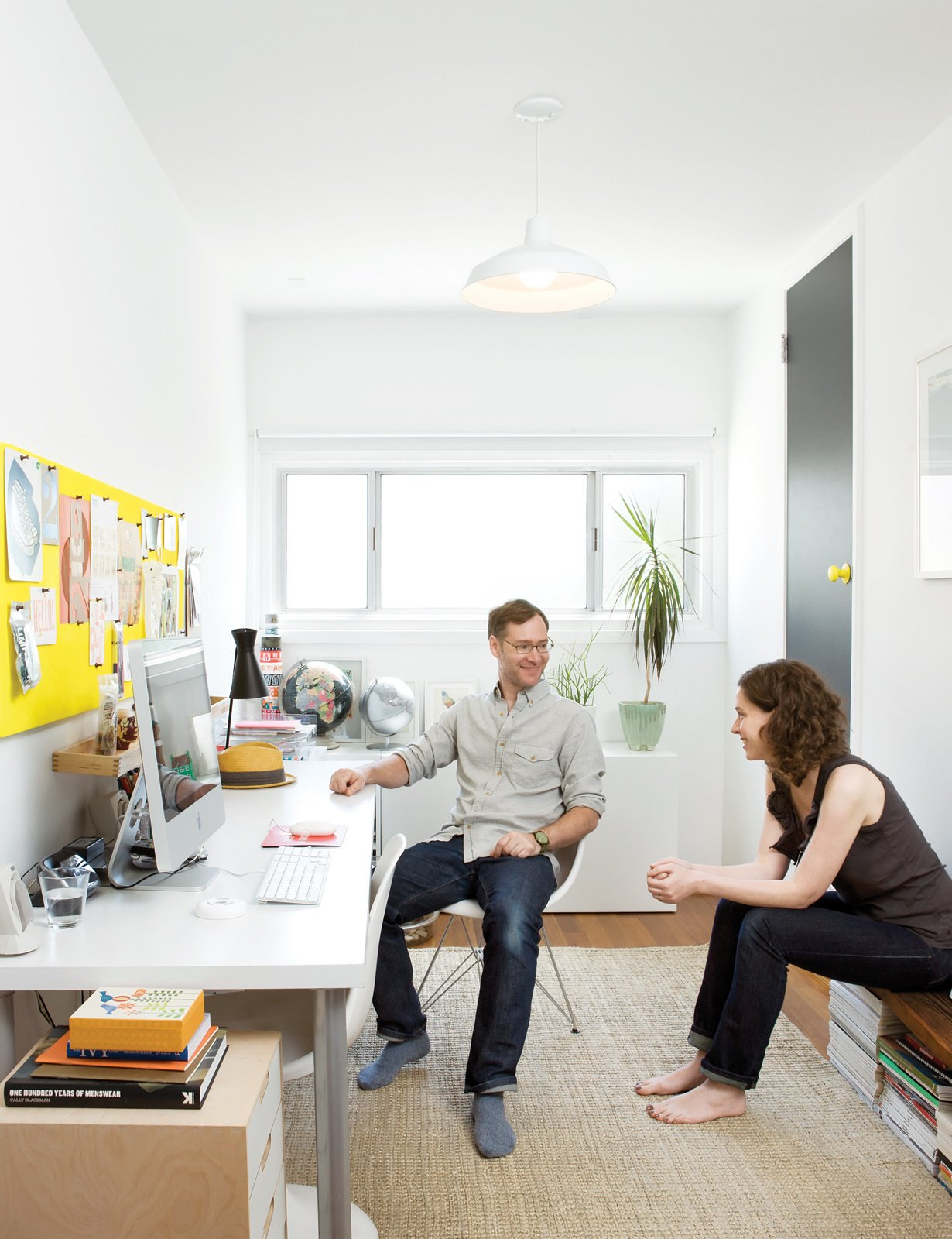 What was once a storage space is now a sun-drenched home office where the couple writes emails and stores their design magazines. The jute rug is from West Elm; the desk is a door on Ikea legs. Tagged: Office, Desk, and Chair.  Office by Alumnistore from A Couple Tackles Conversion Challenges and Builds a Modern Renovation