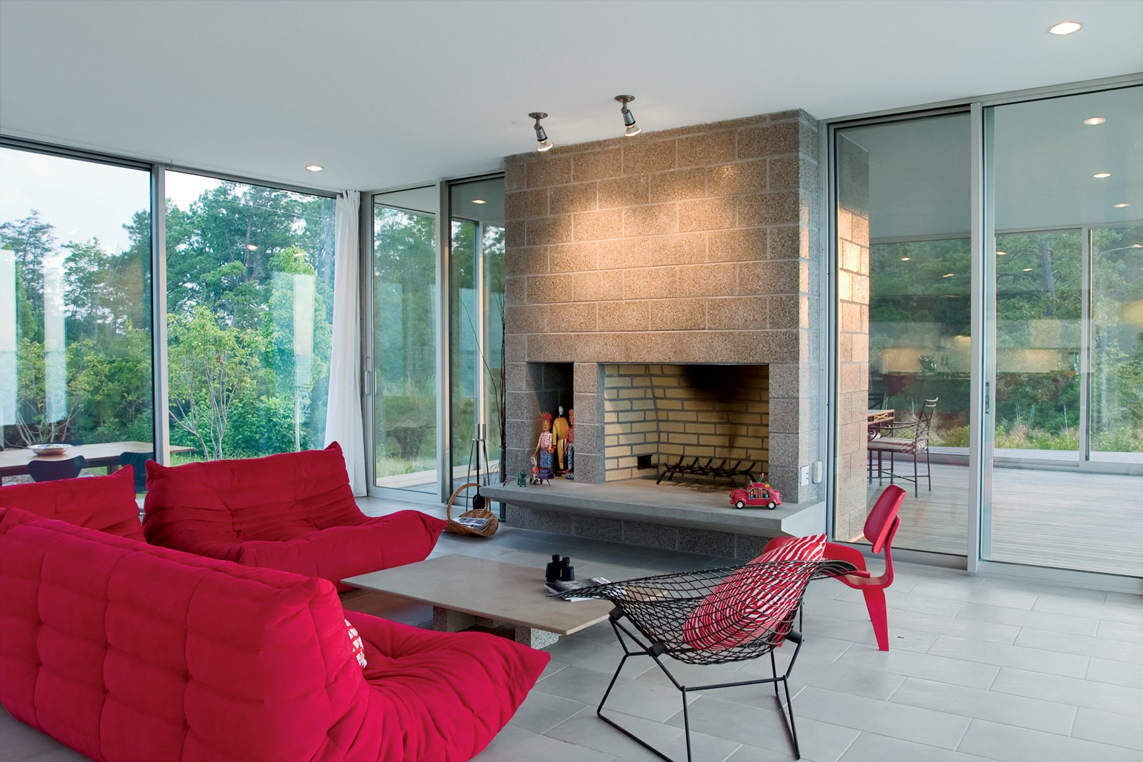 Magenta Togo sofas by Ligne Roset, a red Eames molded plywood chair, and wire Bertoia Diamond chair provide seating around the hearth. Tagged: Living Room, Standard Layout Fireplace, Wood Burning Fireplace, Chair, Ceramic Tile Floor, Sofa, Ceiling Lighting, and Coffee Tables.  Photo 1 of 2 in Row House