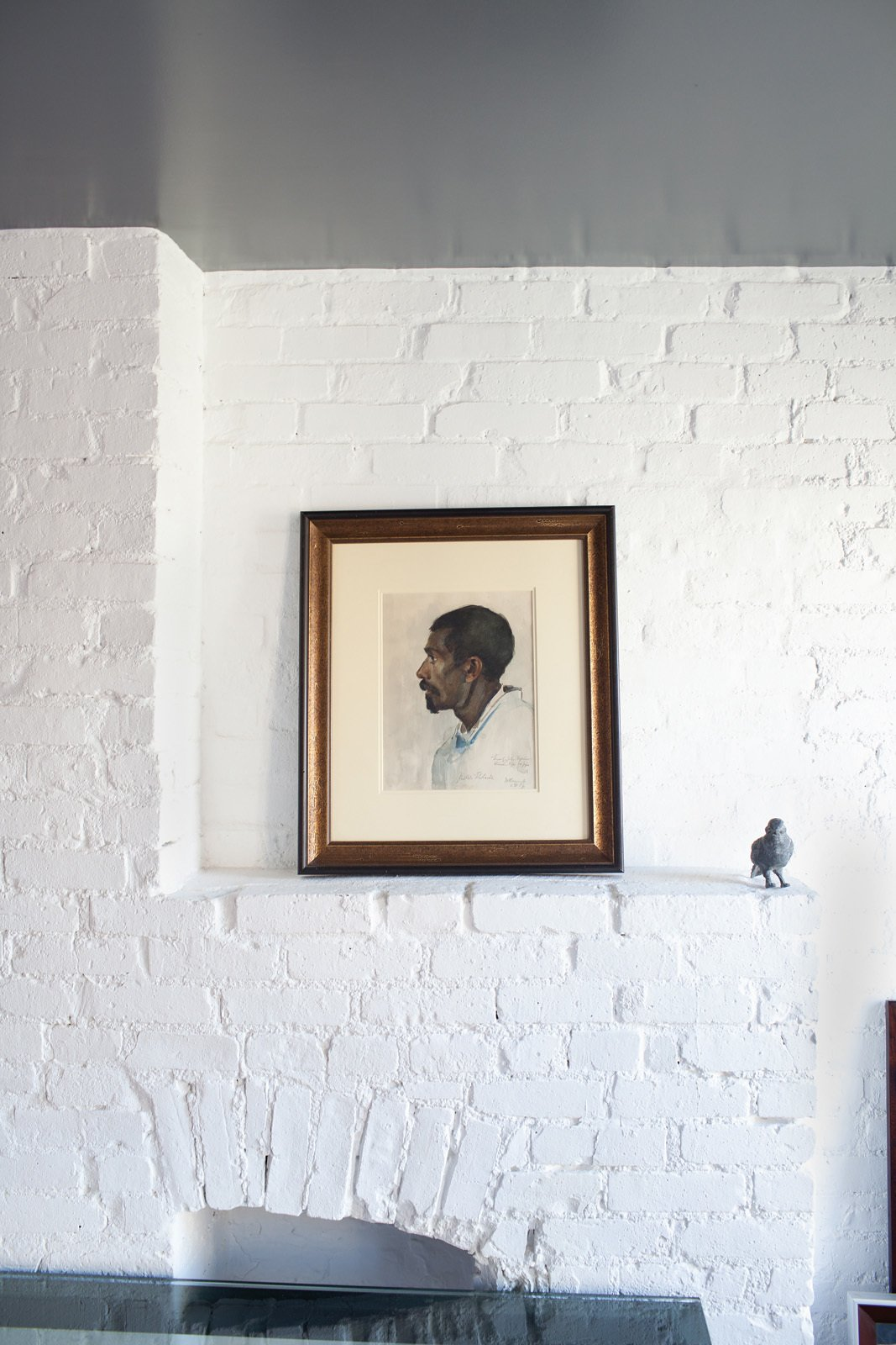 The peaceful space is accented with art, like the watercolor portrait gifted to the couple.  Photo 3 of 10 in Revealing the Pros and Cons of Exposed Brick and How to Take Care of It from Tunnel Vision