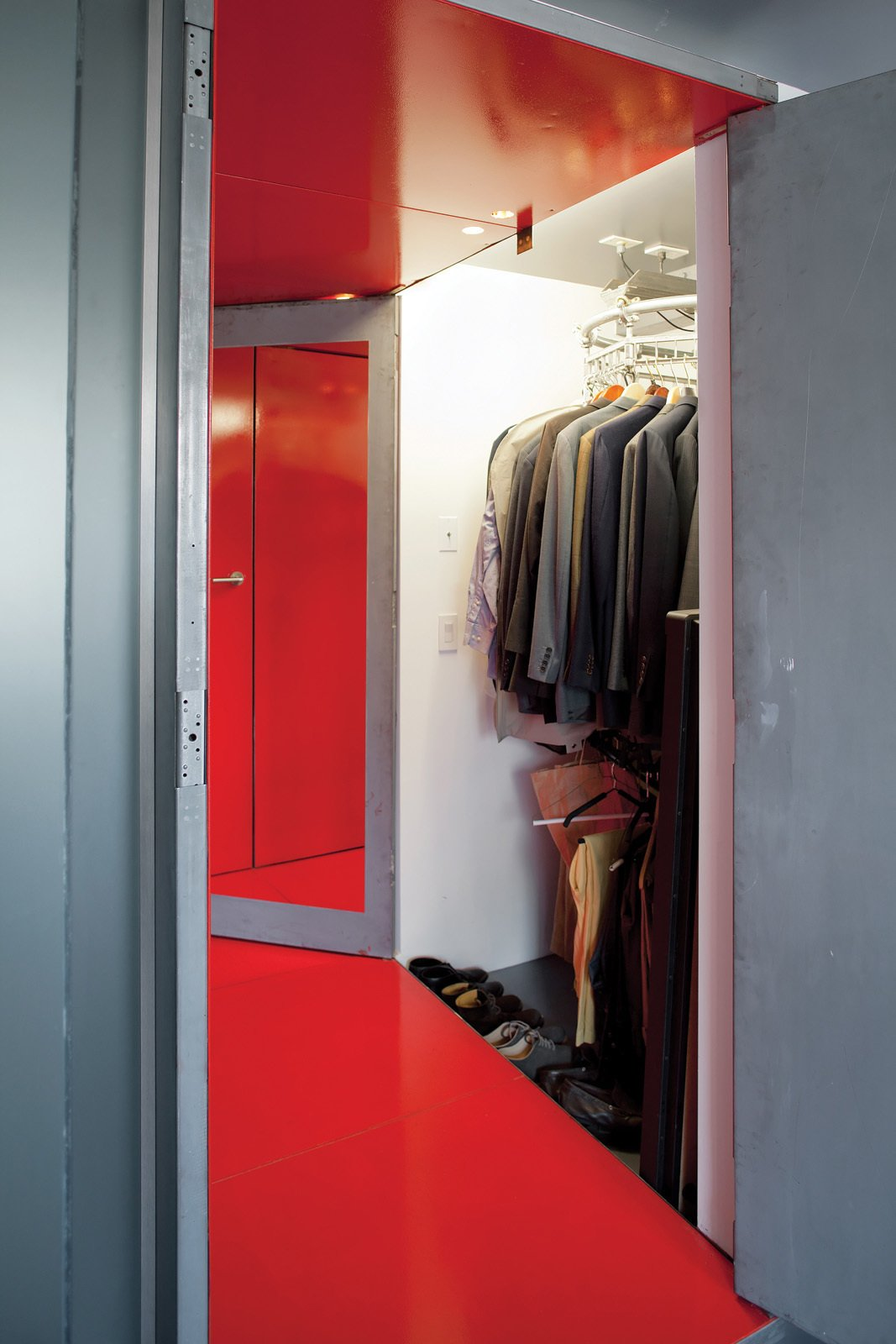 """Fontanez solved LOT-EK's conundrum of how to situate the bed against the center wall while still maintaining closet access by suggesting an automated dry-cleaning rack in the narrow closet. He and Russell access the closet from opposite ends. """"We just have to make sure we don't spin it at the same time,"""" Fontanez says.  Don't miss a word of Dwell! Download our  FREE app from iTunes, friend us on Facebook, or follow us on Twitter!  Photo 10 of 10 in Tunnel Vision"""