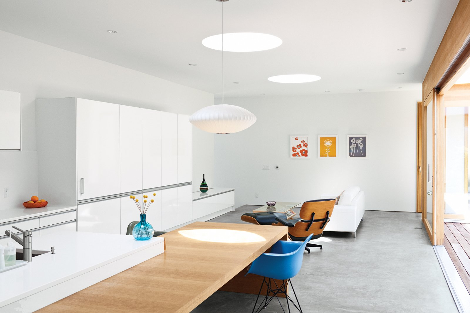 A handful of modernist classics—an Eames Lounge, a Bubble Lamp by George Nelson, and a shell armchair from Modernica—kit out the living room and kitchen.  Photo 5 of 19 in Looking Inward