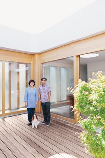 "Paul and Shoko stand on the ipe deck with their dog, Mei. ""At first, we really wanted an Eichler, but it just did not work out. But after seeing a few we knew we had to have a courtyard home,"" says Paul."