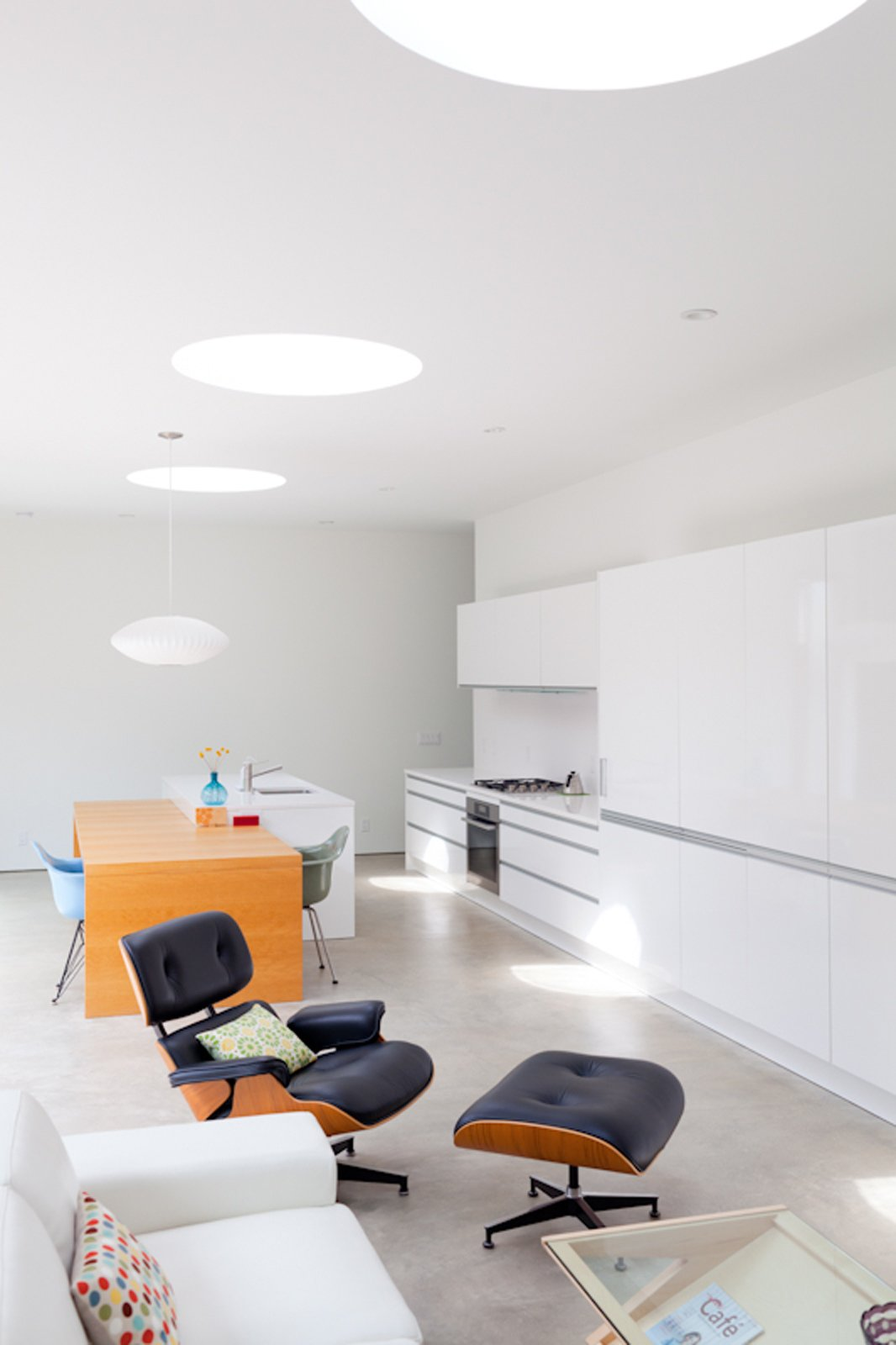 Though loads of natural light comes in from the courtyard, these large skylights also afford a view of the sky. The coffee table is from Modernica and the Eames Lounge is from Herman Miller. Tagged: Living Room, Ottomans, Concrete Floor, Sofa, Recliner, Recessed Lighting, Pendant Lighting, and Table.  Photo 17 of 19 in Looking Inward