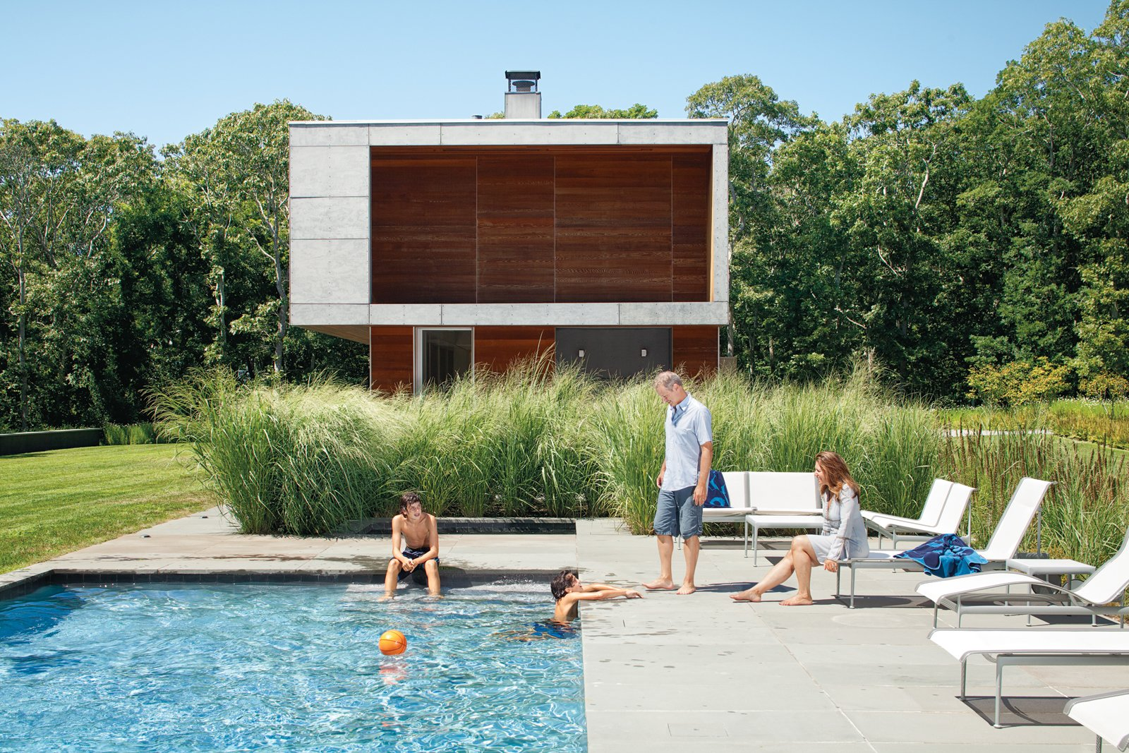 The Pryors relax at their Montauk retreat among modular furniture from Richard Schultz's Swell Seating Collection and chaise longues from his 1966 collection from Knoll. Tagged: Outdoor and Swimming Pools, Tubs, Shower.  Photo 1 of 10 in 10 Sunny Poolside Prefabs