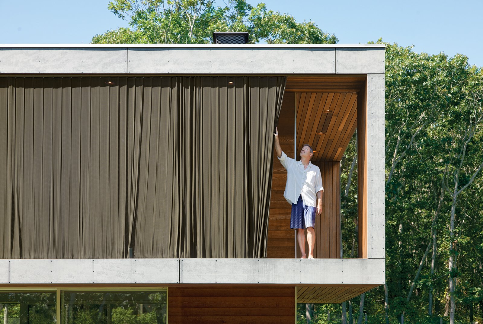 Two layers of aluminum woven-coil drapes hang outside the large, south-facing windows above the living area.  Photo 2 of 7 in Green Sustainable Home in Montauk