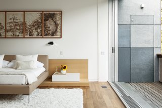 In the bedroom, walls painted with benjaminmoore.com Aura matte paint complement the insulated concrete panels that clad the exterior walls. The floors are walnut, and sealed with Osmo Polyx-Oil, a finish made with sunflower, soybean, and thistle oil.