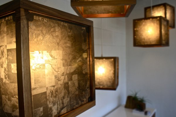 """""""These hanging lights are framed in walnut and made from original 1960's glass negatives of the Texas landscape taken from a survey plane,"""" says Rob McGowan."""