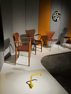 A Cherner Chair Retrospective - Photo 16 of 23 - In one corner of the show, a bright yellow Vola faucet, designed by Arne Jacobsen and Teit Weylandt in 1969, holds court with a tribe of wooden chairs from the 1940s and 50s.