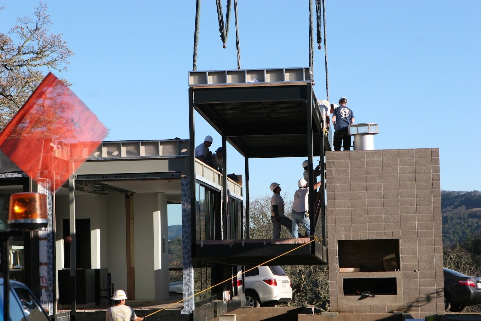 Here's one of the outdoor covered deck modules being lowered into place adjacent to the fireplace.  Building a Prefab House by Jaime Gillin
