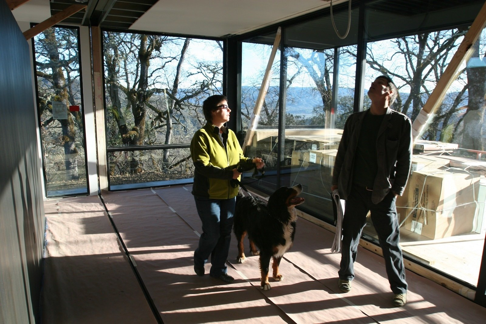 """Abbie, Stella (the Burton's other dog), and Riley, the project architect for Marmol Radziner, stand in the master bedroom, just after the last module was set. """"You can see the open drywall seam in the ceiling that will be closed up over the next six weeks,"""" Bill points out.  Building a Prefab House by Jaime Gillin"""