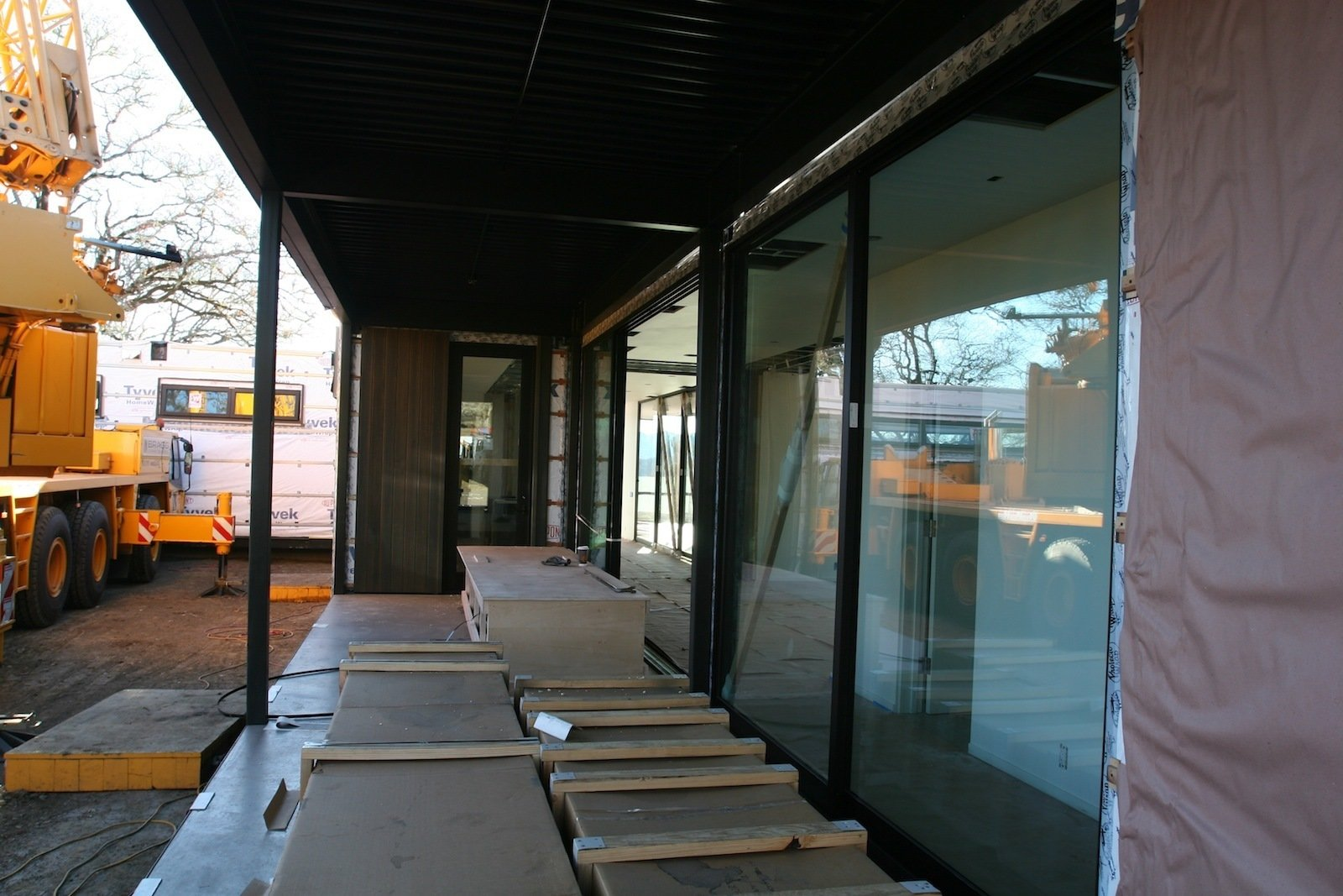 A view down the length of the outdoor covered deck leading to the front door.  Building a Prefab House by Jaime Gillin