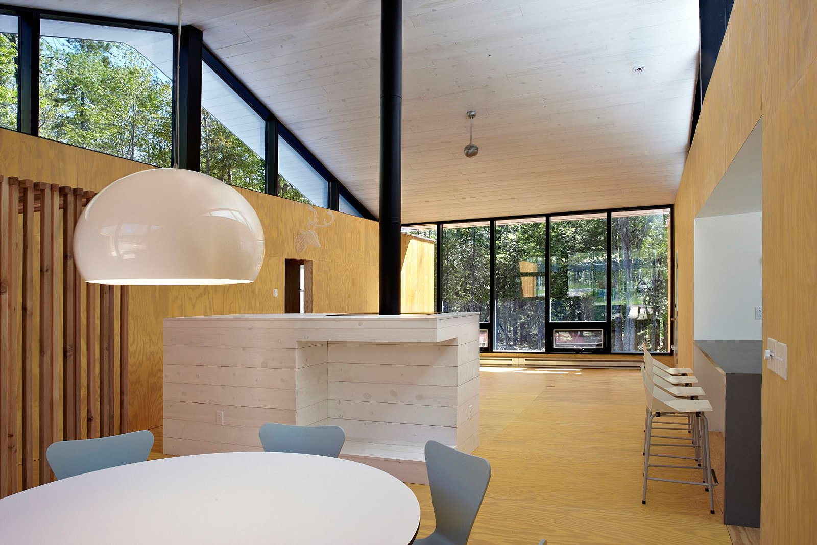 In the naturally lit central living space, stained plywood is used for the walls and flooring. The interior boasts high ceilings, a wood-burning fireplace, and a dining table by Robert Ewert Designs.  Blu Dot Spotted by Blu Dot from Superior Logic