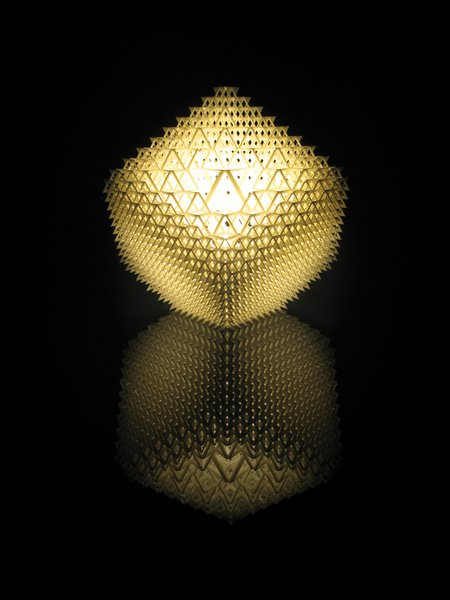 "Shine a LightBenshetrit's table lamp, for the lighting and furniture company .MGX by Materialise uses QuaDror's infinitely scalable geometry to create a honeycomb of 1,200 modules that fits over a metal base holding a 40-watt halogen bulb. The lamp, which arrives flat and expands, accordion-like, when lifted, is manufactured via selective laser sintering (SLS), a 3-D printing process that uses a laser to solidify layer upon layer of powdered resin particles. ""When you buy the lamp, you get a disc with the file on it, so if it breaks, you can 'reprint' it,"" Benshetrit says."