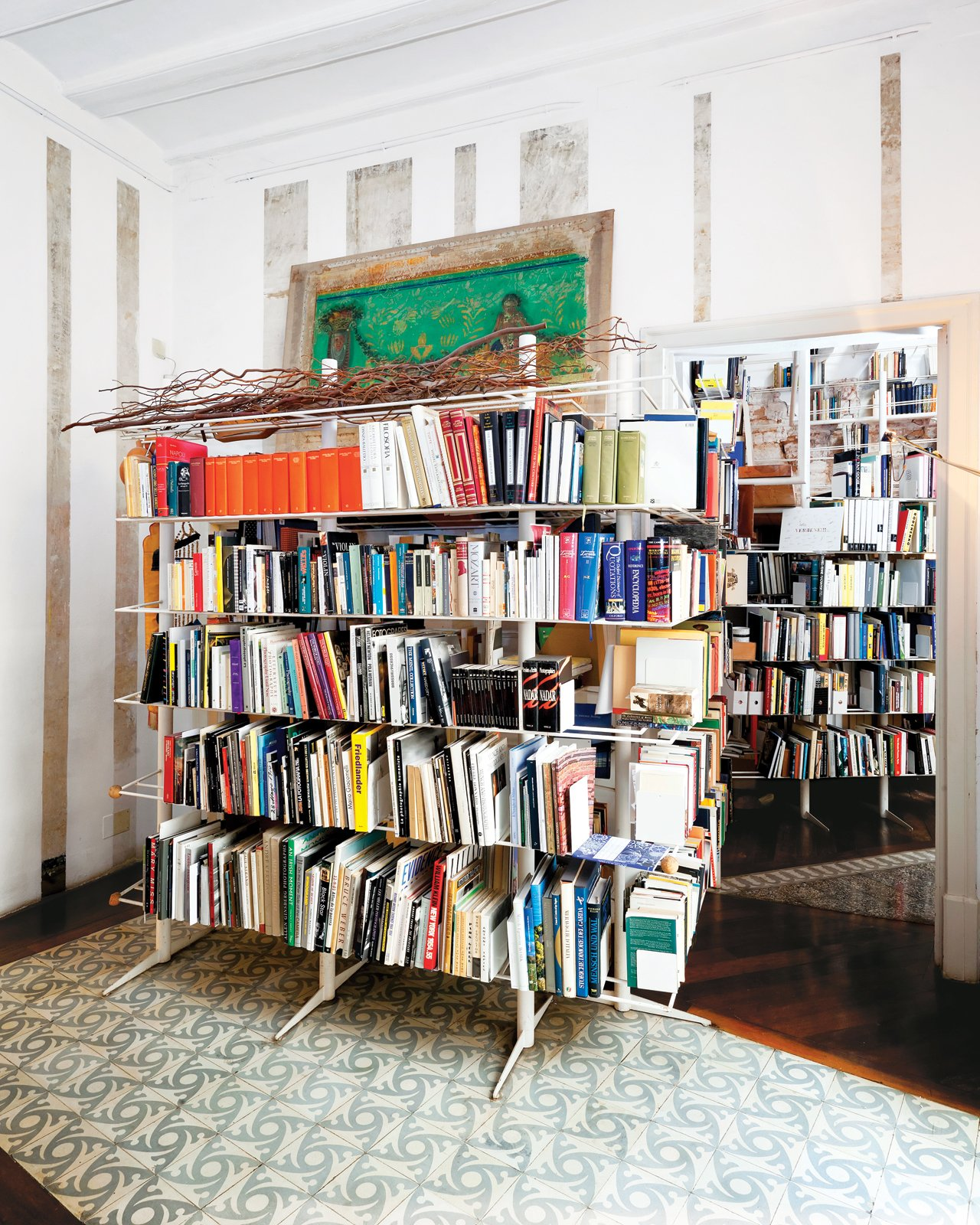 Freestanding shelving by Miralles holds yet more tomes from the family's prodigious collection. Irregularly placed tilework on the floor follows the trajectory of the sun's rays as it travels across the room.  30+ Modern Homes With Libraries by Matthew Keeshin from The Barcelona Home Like No Other