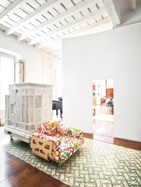 Paths of Andalusian tile and intervening plaster walls help to delineate space in the expansive apartment, which is centered around an internal entry courtyard. The armchair, designed by Peter and Alison Smithson, is covered in a Josef Frank textile from Just Scandinavian. The white piece just behind it is a repurposed Austrian stove that's now used as a storage device.