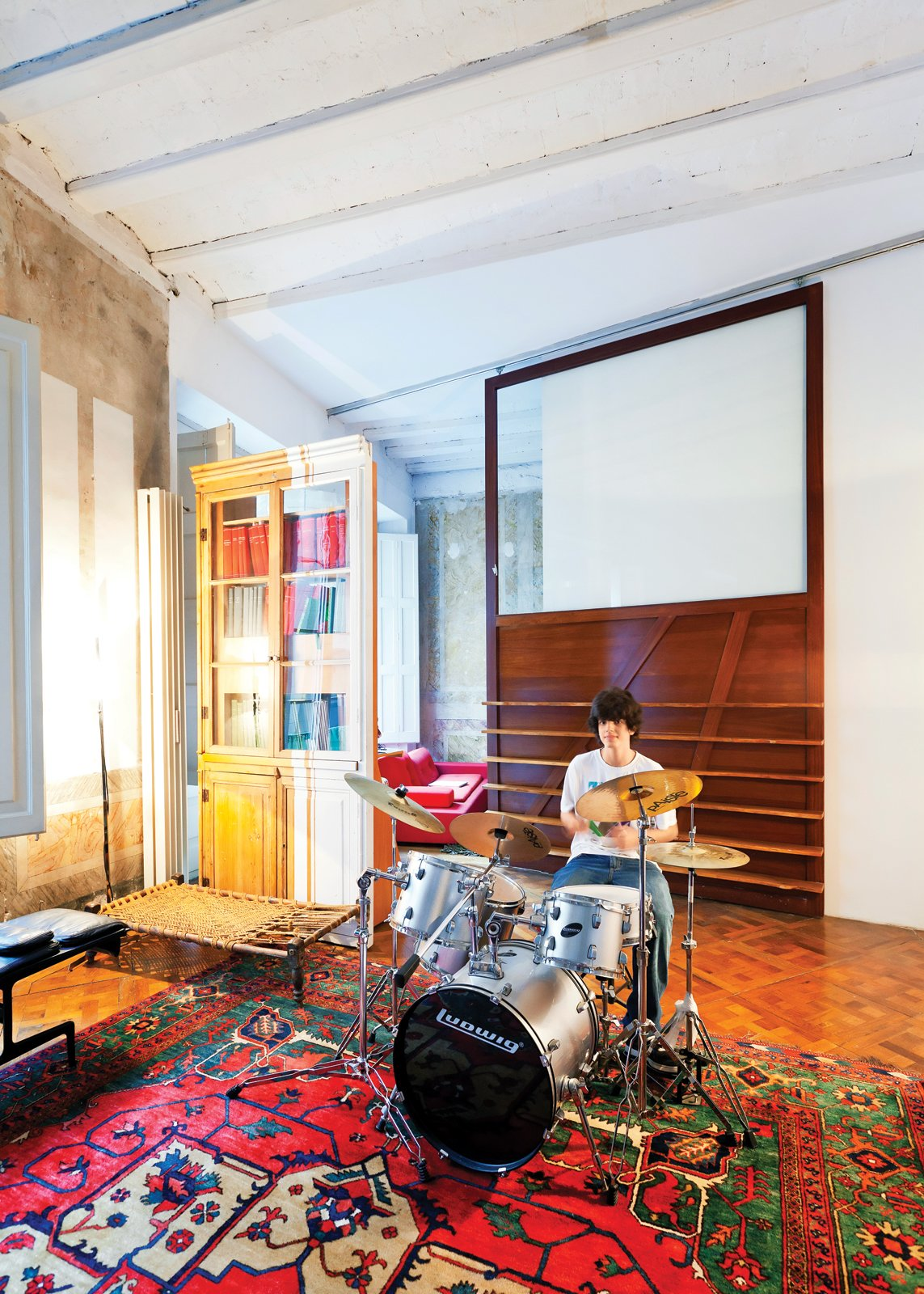 In one area of the apartment, Tagliabue's son, Domenec, plays drums in front of a sliding wood panel of the architects' design. Tagged: Kids Room.  Photo 9 of 23 in The Barcelona Home Like No Other