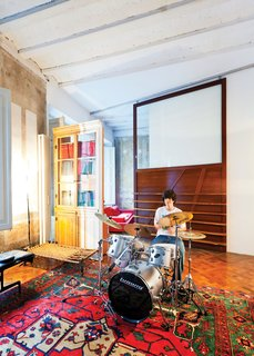 In one area of the apartment, Tagliabue's son, Domenec, plays drums in front of a sliding wood panel of the architects' design.