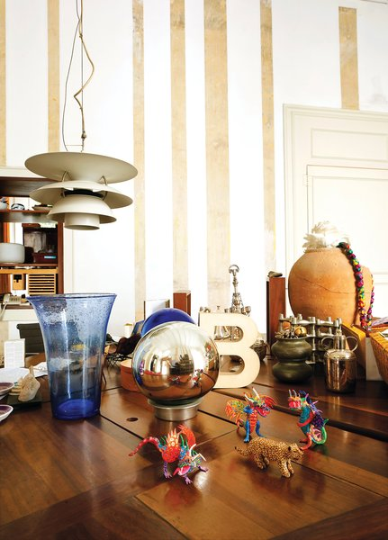 "Resting atop an oak table by Miralles, amidst a collection of tchotchkes, is the ""B"" trophy awarded to the pair for their work on the Santa Caterina Market rehabilitation project. A Louis Poulsen lamp hangs just above."
