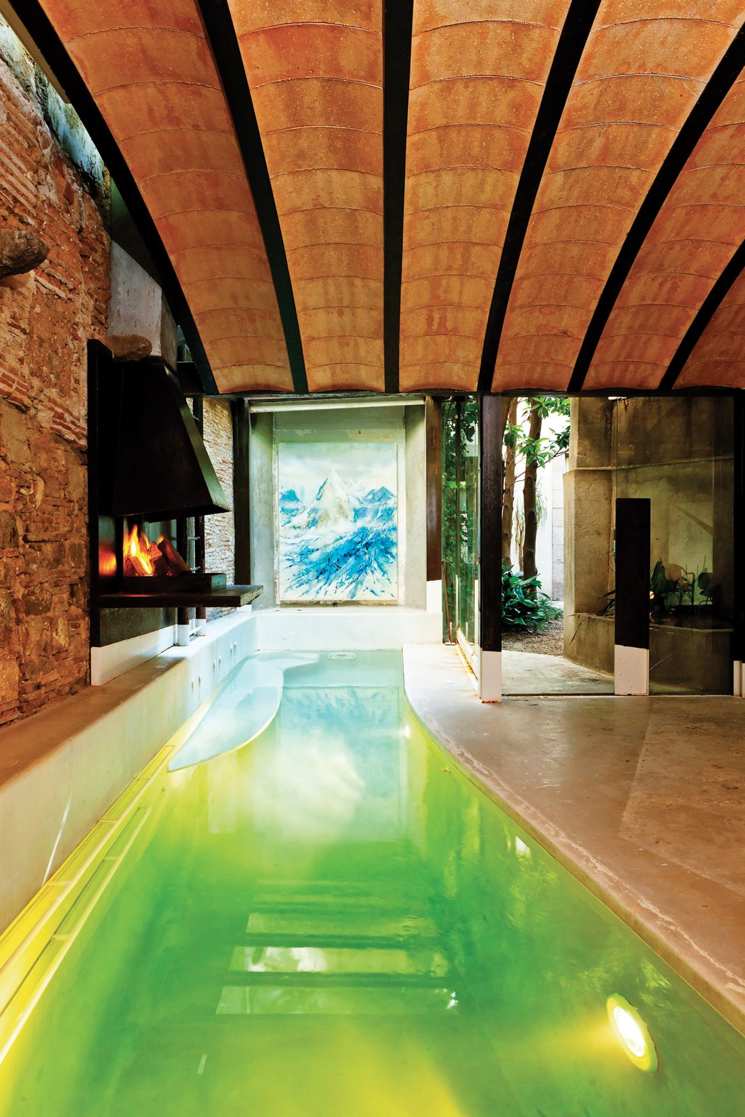 One of the most significant architectural developments within Tagliabue's property   is the pool house, which features a shallow lap pool and a wood-burning fireplace.  Photo 13 of 23 in The Barcelona Home Like No Other