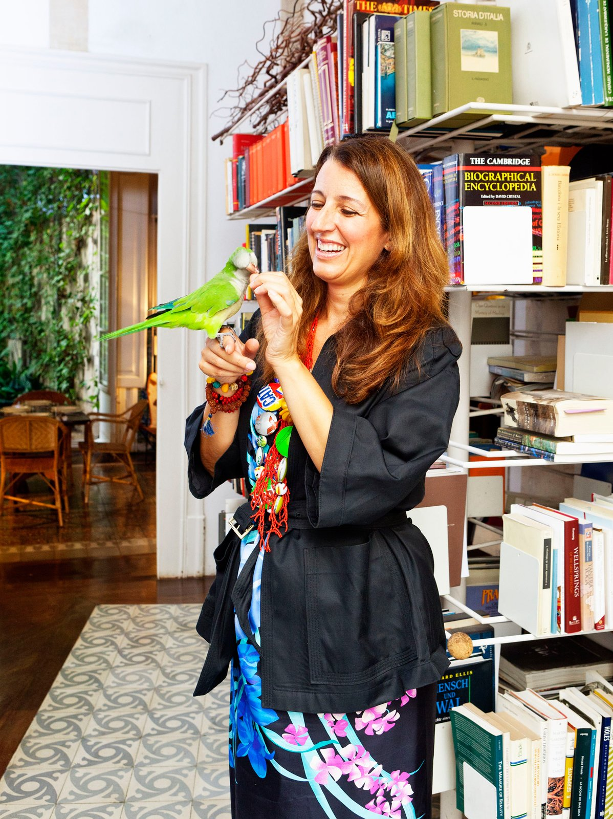 Benedetta poses with her pet bird, who keeps watch on the entrance courtyard below from his perch in the library. Tagged: Office, Shelves, Library, Bookcase, Dark Hardwood Floor, and Rug Floor.  Photo 22 of 23 in The Barcelona Home Like No Other