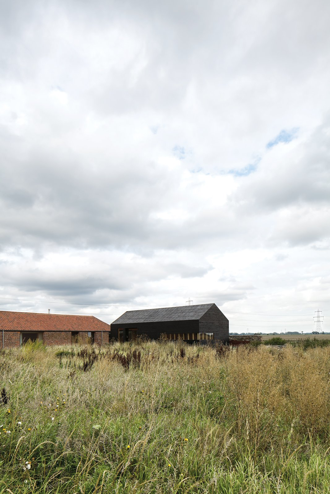 Tucked away in a corner of Norfolk County, England, this pair of barns—one new, one renovated—sit low in the vast countryside. A Pair of English Barns Hide Unabashedly Bold and Budget-Friendly Minimalist Interiors - Photo 1 of 12