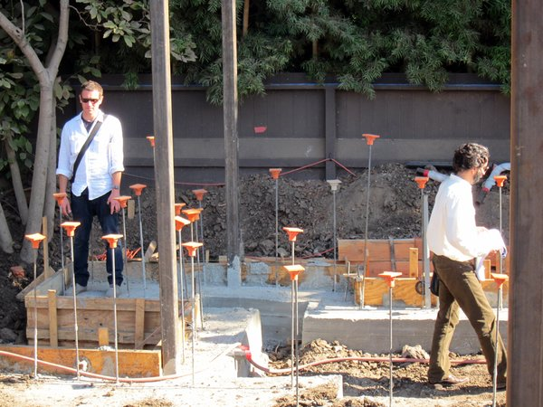 Project Manager Jeff Svitak and Designer Sebastian Mariscal inspect the poured footings, steel posts and plumbing.
