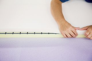 Ruché Sofa - Photo 6 of 11 - A technician sprays a sheet of pliable purple memory foam with a water-based adhesive and then carefully folds it over the other two foam layers and a steel spring grill to complete the backrest.