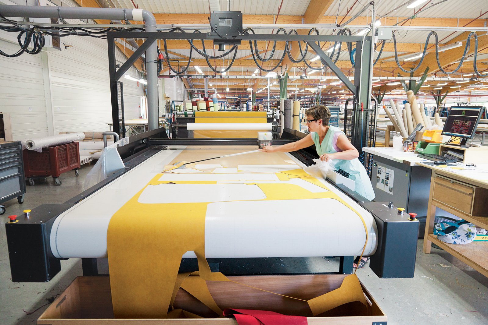 A seamstress mans the automated Gerber Cutter, which cuts patterns precisely and in a way that minimizes wasted fabric.  Photo 7 of 11 in Ruché Sofa