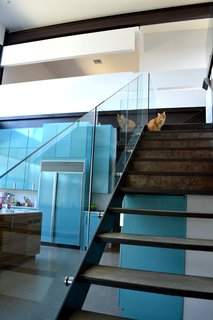 The steel-framed stair with concrete treads and glass guardrail makes a nice perch for the family cat to take in views of the lake and check out what's cooking in the kitchen. Photo by J.C. Schmeil.
