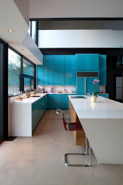 Lacquered turquoise cabinets are topped by white quartzite countertops. Photo by Brian Mihealsick.