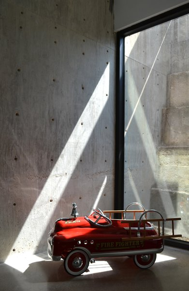 The concrete retaining wall at the back of the living room and dining area registers the passage of the day through a constantly changing play of light and shadow. Photo by J.C. Schmeil.