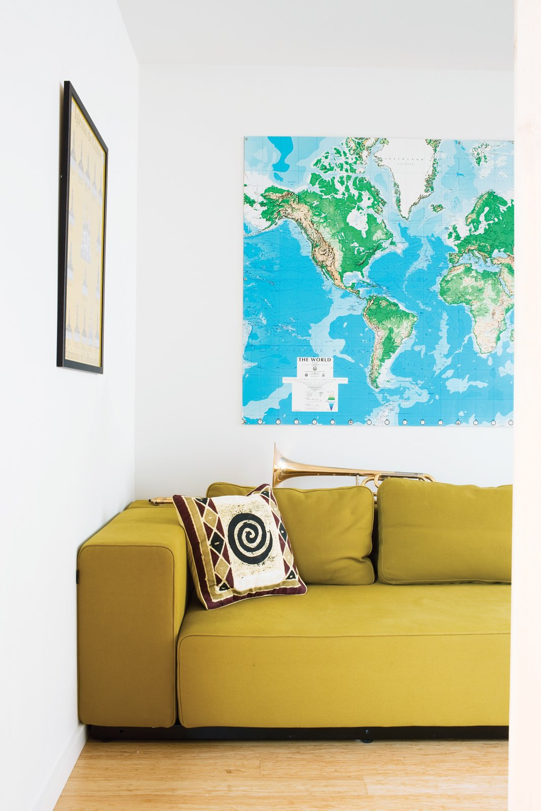 A mustardy couch and a large map of the world—Whitlock travels all over the place for work—keep the living room bright and cheerful. Tagged: Living Room, Sofa, and Light Hardwood Floor. A Sound Professional Goes DIY While Building an Affordable Montana Home - Photo 9 of 16