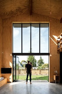 "Take a Step Through 20 Huge Modern Doors - Photo 2 of 20 - Davor and August check out the yard from the living room. ""The bifold Vistalite doors allow us to open the house up completely and enjoy the fresh, warm air,"" Davor says."