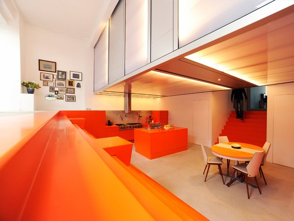 """The kitchen and dining area and is surrounded by orange steps that function as seating. The dugout allows for a second level used for the bedrooms, which are housed in a polycarbonate """"lightbox."""" Photo 2 of Parksite Residence, Rotterdam modern home"""