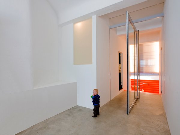 The home's different levels create a playful experience for the inhabitants. The concrete floor references the building's past use as a garage for ambulances. Photo 3 of Parksite Residence, Rotterdam modern home