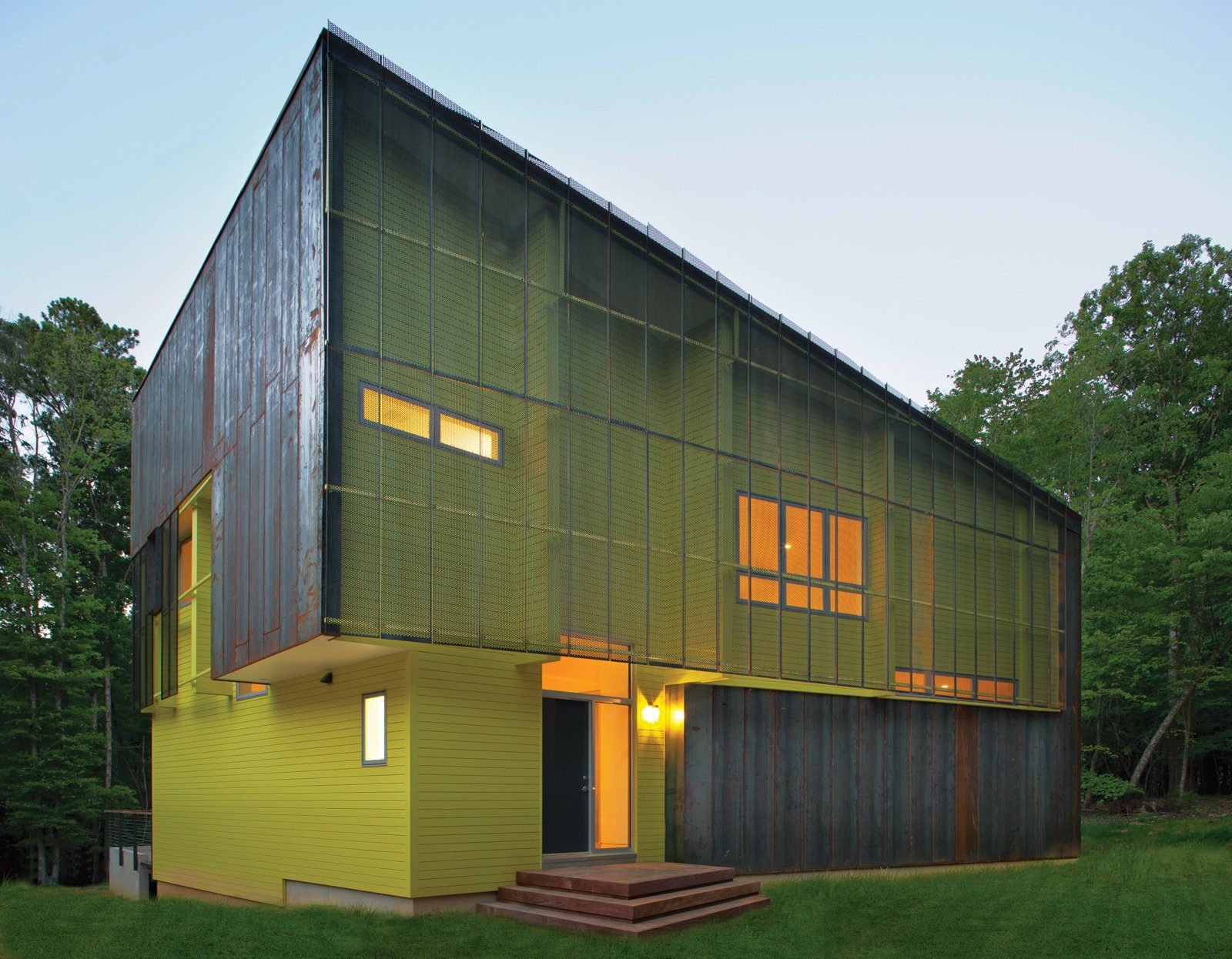 Tuned into its sylvan setting, this affordable green home in Hillsborough, North Carolina, is a modern take on the surrounding centuries-old structures. The bright green paint on its facade contrasts with the Cor-Ten steel cladding.  Photo 1 of 2 in Region of Honor