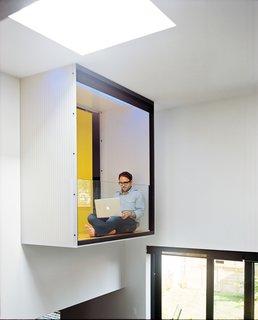 Raymond takes a break on the master bedroom's interior balcony, which is cantilevered over the dining area.