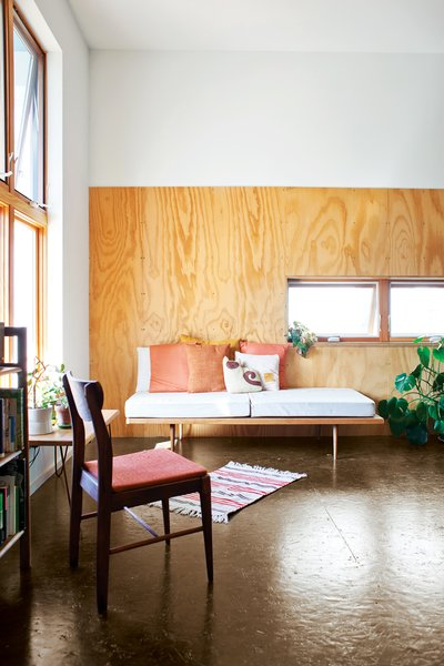 "A peek into two rental units reveals simple but strong interiors. The architects clad the walls with polyurethane-coated plywood ""to provide a durable and attractive finish and provide visual separation between the two levels in the high volume,"" says Shelton."