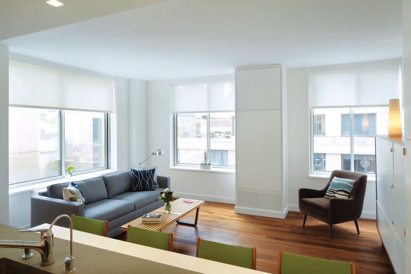 Like a Murphy bed, the dining table tucks into the wall when not in use. Tagged: Living Room, Medium Hardwood Floor, Sofa, and Chair.  Tiny Apartments in New York City by Allie Weiss from Hide and Eat