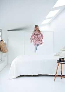 Light-Filled Family Home Renovation in Copenhagen - Photo 8 of 23 - Maja demonstrates another use for the guest bed: a trampoline. Behind her is a wall of storage, an essential attribute in the 1,260-square-foot house. Extreme editing of material possessions also helps.