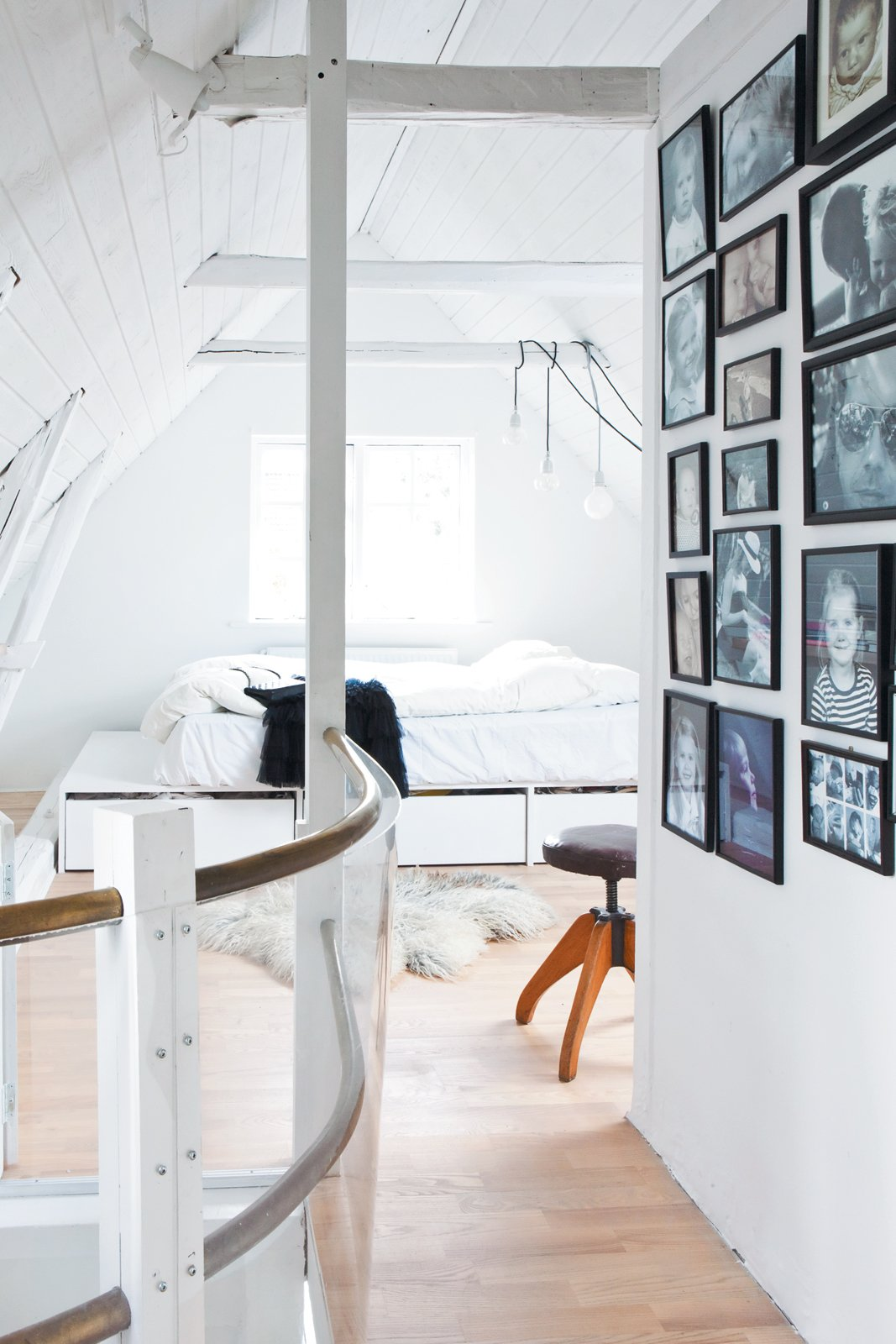 The snug attic contains the couple's platform bed, custom designed by Bjerre-Poulsen to maximize storage and fit the unusual space.  Bedroom by Ashanti Ford from Light-Filled Family Home Renovation in Copenhagen