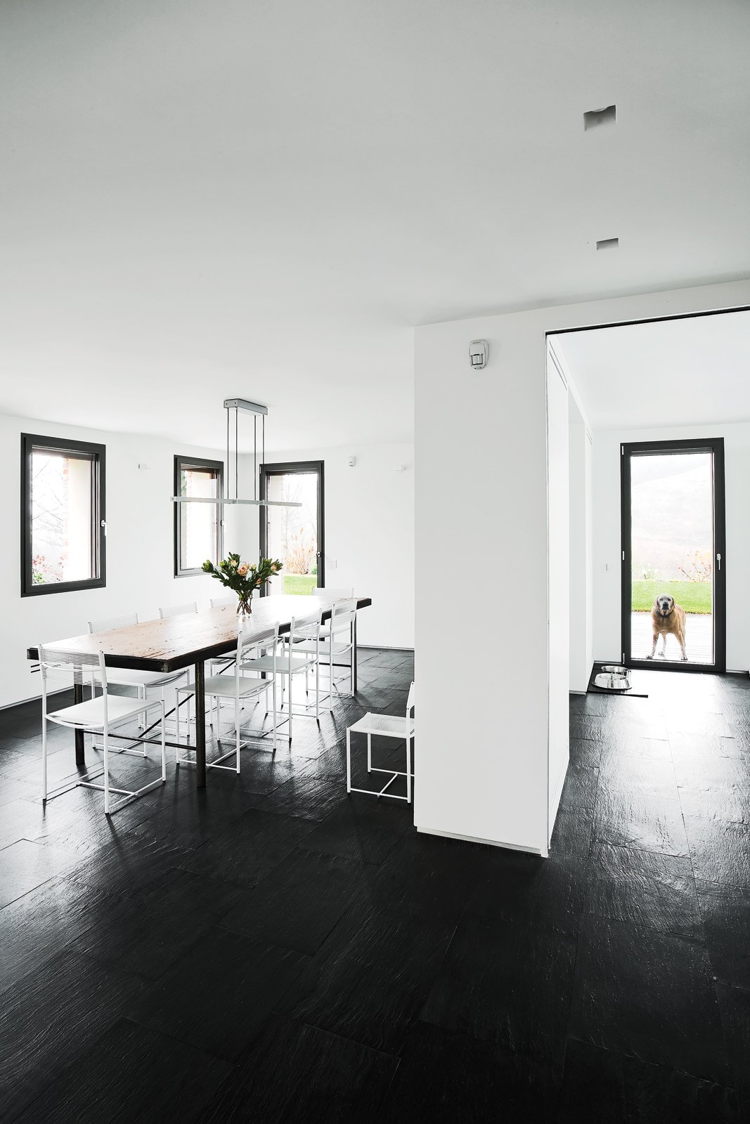 In the dining area a vintage table from a shop in Barcelona is surrounded by Giandomenico Belotti Spaghetti chairs. The space, which also includes the kitchen, occupies a 1970s addition. Tagged: Dining Room, Dark Hardwood Floor, Table, and Chair.  Photo 11 of 11 in 10 Exquisitely Modern Homes in Italy from A Renovated Farmhouse in Northern Italy